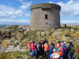 Heritage Week event on Ireland's Eye organised in conjunction with Clean Coasts. Image shows a group of people in front of the martello tower on Ireland's Eye.
