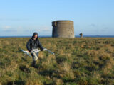 Discovery Programme staff carrying out geophysical survey at Drumanagh Fort, Co. Dublin. Image shows a staff member carrying geophysical equipment with a martello tower in the background and a lighthouse on an island in the distance.